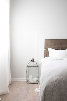 light grey walls, light wooden floor, white curtains, grey/white duvet, grey wood headboard, yellow chevron cushion, black and white deer cushion, branch curtain holders, woodland creature night lights, nothing on mirrors, white trimming on bottom of walls