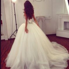 Ball gown with beaded corset bodice, dropped waist, and full tulle skirt, and chapel train.