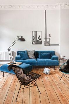 Jouer sur les murs avec une decoration au masking tape qui prolonge la deco murale et l'affiche minimaliste dans ce salon canapé en velours bleu canard.