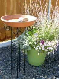 Easy birdbath made from repurposed CD tower and a saucer weighted with rocks!