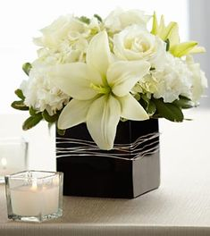 The FTD® State of Bliss™ Arrangement is an ideal centerpiece or accent piece for the wedding reception. White roses, Asiatic Lilies, carnations and hydrangea are offset by lush greens and arranged in a designer black ceramic cube vase to add to the elegant ambience of this most momentous day.