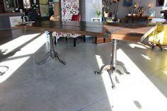this table is made from reclaimed pine wood beams from a church in indianapolis that were cut into planks and refinished. the edges were kept original and sealed. metal strapping was welded to hold the wood together and inlaid flush on top and sides. a pair of matching antique dietzgen cast iron drafting table bases make up the legs. it adjusts in height. top is 36 x 84.