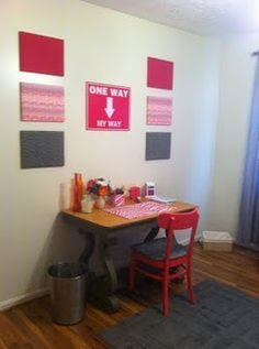 Dirty foam pin boards above her desk, covered with fabric.