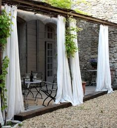Mediterranean patio with outdoor white curtains by Tongue in Cheek Antiques