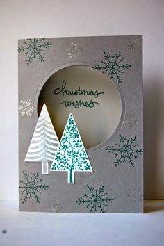 Stampin' Up! ... handmade Christmas card by Julie Kettlewell ... gray base with  silver and teal ... open circle window shows sentiment inside ... two punched triangle trees anchor it ... luv the design balance ...