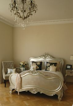this bedroom has an ornate silver bed, herringbone floor, chandelier & great molding...