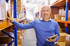 Portrait of a mature man working inside in a distribution warehouse - stock photo #1182037