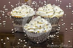 Some white cupcakes with silver sprinkles sitting on a reflective table    Also http://youngadults.about.com/od/graduationtips/ss/Silver-Wedding-Anniversary.htm