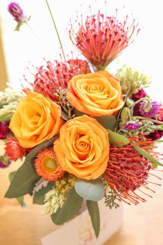 Fall floral arrangement for a Home Grown Bloggers conference. Orange roses, red protea, pin cushion flower, purple wild flower, cockscomb, dusty miller, seeded eucalyptus, rustic. By Gold Leaf Floral // @goldleaffloral. Photo by Joy Leigh Photography.