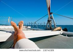 woman lounging on a catamaran sailboat trampoline with her feet propped up and crossed.  calm blue ocean and cloudless blue sky are in the background. copy space available - stock photo