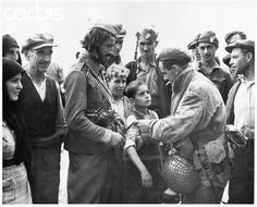A Greek boy who survived the Nazi massacres in his area looks at his British liberator (who pins a Union Jack on his sleeve).