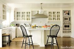 "the black Windsor chairs for contrast — ""like a punctuation mark"" — in the creamy room, painted White Dove by Benjamin Moore. Tiles, sinks, and faucets are by Waterworks. Stone and wall oven, warming drawer, microwave, and hood are Viking. The ..."