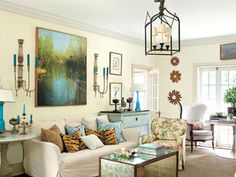Largely white living room with colorful accents, , a landscape painting over the bed, and a lantern chandelier
