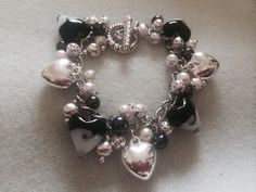 Black, White and Silver Love and Roses bracelet.. Black and white lampwork hearts, silver charm hearts, silver filigree rounds, round rose charms, silver ball spacers, silver bubble spacers, black glass pearls, white glass pearls, silver clasp.
