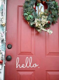 A festive red door decorated for Christmas using Command products.