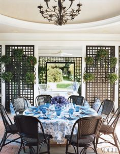 Tory's table in the poolhouse dining rotunda is set with D. Porthault linens and Mottahedeh Tobacco Leaf china.