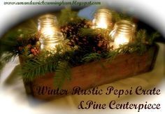 Pine Box Christmas Centerpiece. Old soda crate or something similar, 4 lg Mason jars, fresh pine boughs, pine cones, Epsom salts, berries (fake or real), votive candles in glass. Place jars in box, cut & arrange pine around jars, stick pine cones & berries amongst greenery attractively. Pour Epsom salts evenly between the four jars. Press votive candle down inside jars. Epsom salts look like snow. Different look w/wide mouthed quart jars.