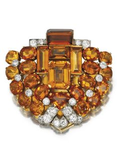GOLD, PLATINUM, CITRINE AND DIAMOND CLIP-BROOCH, CARTIER, LONDON, CIRCA 1935.  Of geometric design set with numerous fancy-cut citrines weighing approximately 20.00 carats, accented by old European and single-cut diamonds weighing approximately 1.25 carats, signed Cartier London, numbered 8423.