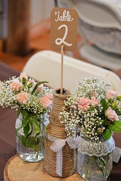 masong jar centerpieces with baby's breath and spray roses sitting on birch wood rounds and with twine wrapped bottles for table numbers