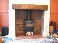 Wood burner with wooden mantle, brick surround and terracotta tiles.