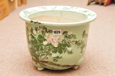 A large Chinese Celadon glaze jardiniere with raised enamel decoration of flowers and foliage. He