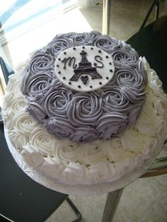 This engagement cake is Paris inspired. It was baked in 2 tiers : 8 inches and 12 inches. The buttercream is applied using the rose cake technique in white and purple. The topper is a fondant circle decorated with purple buttercream piping. This would also be used as a wedding cake with a Paris theme.