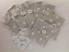 Bolsitas de SweetCo para bautizos con medalla de cerámica personalizada con la inicial del niño.