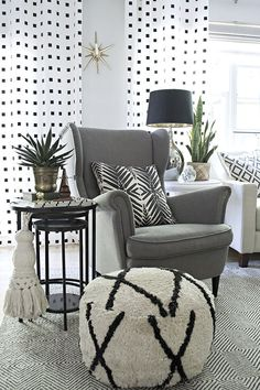 quirky home decor: giant tassel and wooden glasses holder in eclectic black and white living room
