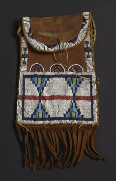 CHEYENNE BEADED AND FRINGED HIDE DISPATCH CASE    composed of commercially tanned leather, thread and sinew sewn in typical colors of glass beadwork, along the edges, and on the front, witha pair of stylized butterflies, surmounted by a frieze of three concentric semi-circles.  length with fringe 11 1/2 in.