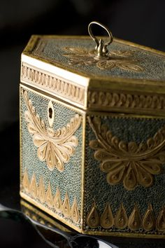 A hexagonal tea caddy is embellished with green and gilded rolled paper, also called paper filigree. Tea caddy courtesy of Sallea Antiques; photograph by Doug Todd