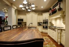 A country kitchen with an enormous all-wood multi-toned kitchen island with seating for six.  The mantle above the cooking area has potted plants and a charming sign. On either side of the stove are carved pillars that add even more charm to this cozy kitchen.