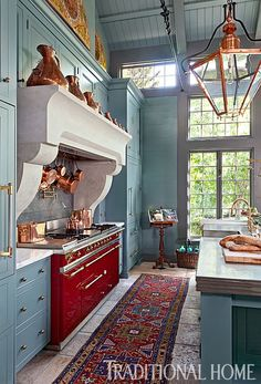 Custom-painted Rutt cabinets conceal appliances and frame the French Lacanche range and Artistic Stone hood. - Photo: Emily Minton Redfield / Design: Rochelle Warner