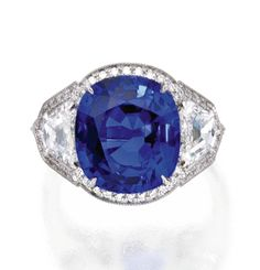 PLATINUM, SAPPHIRE AND DIAMOND RING    The cushion-shaped sapphire weighing 9.10 carats, flanked and framed by shield-shaped and round diamonds weighing approximately 1.25 carats, size 6½.