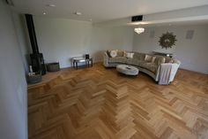 Home living room with Oak Parquet floor, wood burning stove on flush hearth with hidden projector and drop down cinema screen. Flush wall mounted speakers.