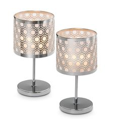 """Enchanted Silver Mini Votive Lamp Pair  Item #:  P90999S        Sleek honeycomb pattern lends a lively energy to your decor. Light a votive, or tealight sold separately, to illuminate the photo-etched metal and mesh shade. Includes glass votive cups. Set of 2. Each 7 3/4""""h, 4 1/4""""dia."""