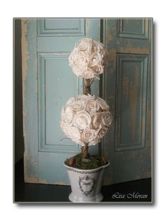 Stunning double topiary with cream Sola roses and set in a dragonfly urn.