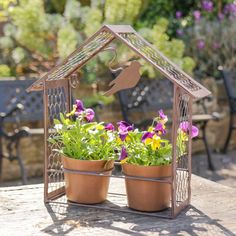 This twin garden planter is perfect for adding decoration and brightness to a home or garden wall. Made from rustic chicken wire and wrought iron which has been finished in an antique brown shade with a decorative bird hanging above the two plant pots to add some extra embellishment to the greenhouse style design. Easily mounted to the wall the frame has two eyelet hooks or can be used as a simple stand to house your favourite flowers and plants.