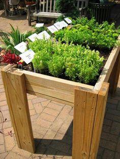 bac à fleurs DIY en bois avec des herbes aromatiques sur la terrasse