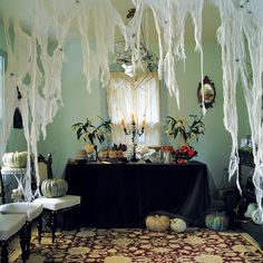 A tangle of cheesecloth spiderwebs is a sure sign that ghouls, goblins, and other spooky types have taken over the (un)living room. The ragged-looking webs can be hung across any entryway. Drooping lilies on the buffet table and pumpkins in faded hues add to this space's haunted appeal.