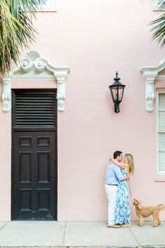Charleston engagement pictures in front of a pink wall with gas lamp and pet…