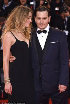 Classy: Amber smiled adoringly at her husband, snuggling into his torso as they posed on the red carpet together