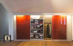 In diesem Beispiel verwenden wir hochqualitative farbige Glasschiebetüren, welche zusätzlich mit einem Leuchtband ausgestattet sind, was einen sehr hochwertigen Eindruck macht. Da das Dach recht flach nach hinten geneigt ist, kommt hier auch unsere doppelte Tiefe mit unseren Schieberegalen zum Einsatz, welche uns noch eine höhere Platzausnutzung erlauben, als es mit herkömmlichen Schränken möglich wäre Feldkirch, Attic, Closet, Home Decor, Interior Lighting, Kitchen Contemporary, Shelf, Loft Room, Armoire