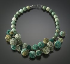 "Shades of turquoise and green ""berries"" cluster gently around the neck."