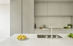 Contemporary grey kitchen. Clean lines and handle-less kitchen cabinets, island with integrated sink and white worktops.