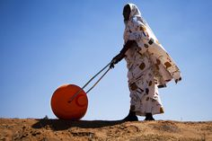 A woman in El Fasher, North Darfur, uses a Water Roller for easily and efficiently carrying water. With its large drum capacity (usually 75 litres), the device frees women and children from having to spend a large portion of every day dedicated to collecting water for their households. The African Union-United Nations Hybrid Operation in Darfur (UNAMID) has distributed some 3,000 such rollers across Darfur. 31 January 2011  El Fasher, Sudan. UN Photo/Albert Gonzalez Farran