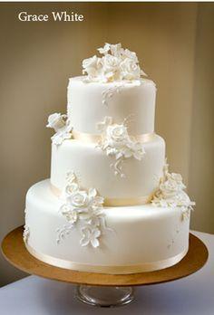 Bolo branco de casamento decorado com fitas e flores de açúcar.
