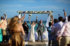 Beach wedding ceremony at Grand Velas Riviera Maya, bride and groom celebrating their love in front of the Mexican Caribbean Sea with a flower-covered chupah.  Mexico wedding photographers Del Sol Photography