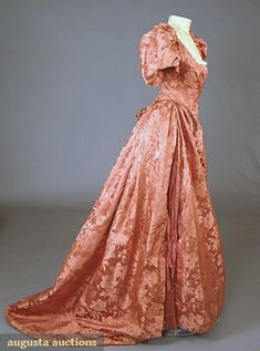 """PERSIMMON SILK BALL GOWN, c. 1895 2-piece, large scale floral brocade w/ pleated plain satin center skirt panel, boned bodice w/ puff sleeve, back laces, points front & back, neckline w/ lace trim, label """"Joseph Johnson Leicester"""", B 33"""", W 20"""", Skirt L 44""""-61"""",excellent."""