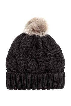 Gorro de malha com lã: Gorro em malha de torcidos de fio macio com uma percentagem de lã. Tem pompom em pelo sintético na parte de cima.