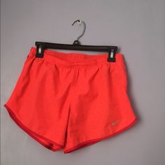 Nike running shorts Super cute gently used Nike running shorts. Bright orange/pink color with little maroon triangles all over. Nike Shorts
